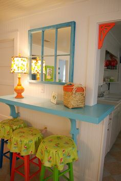 This interior space uses bright colors paired with crisp white walls and cabinets. It's easy to create this whimsical cottage style in your space — all you need is a few quarts of paint and some found vintage pieces, like these wood stools. Beach Cottage Style, Beach Cottage Decor, Coastal Cottage, Coastal Style, Coastal Decor, Beach House, Coastal Entryway, Coastal Bedding, Modern Coastal