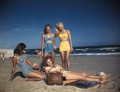 Bathing suit models are shown listening to the radio on the beach, circa 1940s