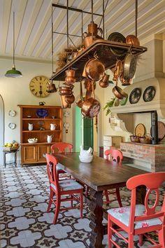 Cadeiras da Tok & Stok, pintadas de vermelho, e mesa de família unem-se na cozinha, com fogão a lenha e piso de ladrilhos hidráulicos, da Ladrilar.  Fotografia: Filippo Bamberghi.