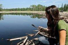 Melina Laboucan-Massimo, scoops up an oily substance from the 2011 Plains Midstream pipeline leak.