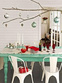 Festive Centerpiece - Branch out from conventional tablescapes by using an extra-long tree limb as a platform for displaying ornaments. Simply knot lengths of twine around the branch and hang it from a row of five or six ceiling hooks. #yule #winter solstice #christmas