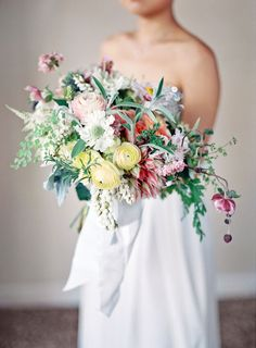 bold and colorful wedding bouquet featuring ranunculus, protea, pieris, ferns, astile and sage by Isari Flower Studio
