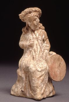 Boeotia  300BC-250BC  Hellenistic  Terracotta figure of a girl seated on a rock, her right hand raised and holding an unidentifiable object, by her left side is a large tambourine, wearing long-sleeved jacket over chiton (perhaps form of Persian kandys), long hair parted at the back to fall in two long tresses, wearing thick stippled wreath.  Coarse pale orange clay, white coating, red on hair and tambourine, gold(?) on vine leaf and girdle, rose-madder and blue on jacket, rose-madder on…