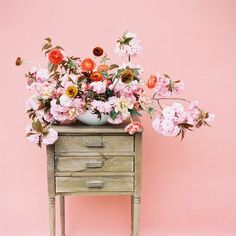 The combination of a simple pink wall, wood drawer, and a floral bouquet creates a romantic and vintage vibe.