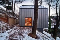 Nanavízió made its debut with this minimalistic, low-key single family home that hides among the ancient trees of the surrounding woods.The steeply sloping w...