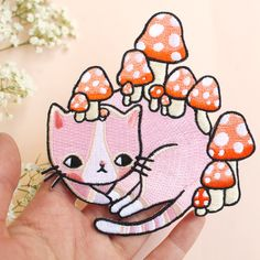 Embroidered mushroom kitty patches! Will liven up any garment <3  Measurements are (width x height) 4,5 x 4 inch or 10 x 11 cm. Comes on card backing.  These patches have an iron-on adhesive layer on the back so are super easy to apply. Once applied, applique is permanently attached to your garment.  How to apply: Set your hand iron at the hottest temperature setting. Do not use steam! Place your patch in the desired position and place a pressing cloth (such as a handkerchief, sheet or…
