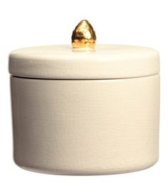 Stoneware container with a crackled finish. Matching lid with gold-colored knob. Height 4 in., diameter 5 in.