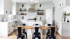 In this kitchen, navy blue Tolix chairs surround a wood and brass dining table under a white pendant light. Light Wood Dining Table, Farmhouse Dining Chairs, Metal Dining Chairs, Dinning Table, Kitchen And Bath Design, Kitchen Decor, Kitchen Ideas, Kitchen Designs, Kitchen Dining
