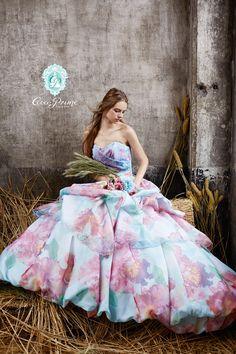 DRESS一覧 | 福岡ウェディングドレスのレンタル「レイジーシンデレラ福岡」  プライムブルー  【New Dress】 優しい色でぼんやり描いた大輪の花は、水彩画のように絶妙な色彩と透明感。身頃とタッキングには、クリアに光るグリッターが施されています。裾のバルーンは上半身をコンパクトに、スタイル良く見えるシルエットです。