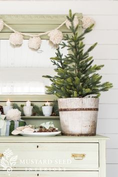 Decorating the new painted dresser for the holidays with moss, ironstone, greenery, pinecones, and white yarn accents, and a small Christmas tree to complete the country cottage look. The furniture paint is Miss Mustard Seed milk paint in Layla's Mint over Lucketts Green, plus Shutter Gray gift boxes. There's even a link to a DIY tutorial for farmhouse pom-pom garland! #paintedfurniture #milkpaint #countryChristmas #farmhousechristmas #missmustardseed