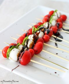 caprese kabobs with balsamic glaze: cherry tomatoes, mozzarella balls, basil leaves, balsamic glaze.