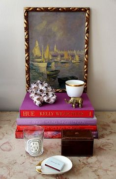 Personal altar. Stacked books and an oil painting become the backdrop for this vignette of beloved objects placed with care.