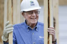 Jimmy Carter resumed his role as Habitat for Humanity's most prominent booster on Monday, donning a white hard hat and a worn leather belt.