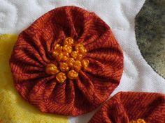French knots in yo yo.  Great idea for flowers.