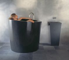 Oval Soaking Tub with Zero Pedestal Sink, Black Granite by Stone Forest | Each design is carved from a single block of stone. #design #interiordesign #interiordesignmagazine #stone @stoneforest