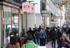 Pedestrians crowd the sidewalk in front of a shopping mall on January 14, 2011…