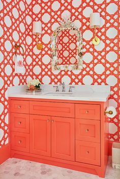 Orange trellis wallpaper lined with orange moldings complements an orange washstand fixed to a marble hex floor and accented with glass knobs and a white quartz countertop. Trellis Wallpaper, Bold Wallpaper, Bathroom Wallpaper, Bamboo Trellis, Powder Room Design, Orange Interior, Bathroom Colors, Bathroom Ideas, Bathroom Interior Design