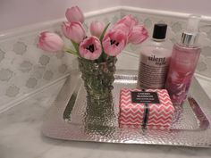 Soaps and a silver tray from HomeGoods add pops of color and sparkle to this sophisticated bathroom makeover.