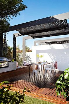 outdoor kitchen and dining with pergola + metal screen for shade   A colourful family home