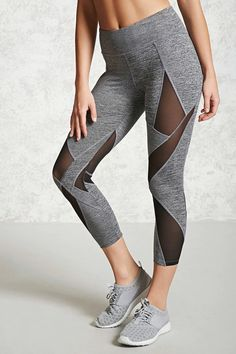 A pair of athletic knit leggings featuring an elasticized waistband with interior drawstrings, a hidden key pocket, geometric mesh paneled detailing, a capri cut, and moisture management wicking fabric.