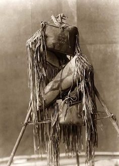Indian Medicine Bags. It was made in 1910 by Edward S. Curtis.    The photo illustrates Four Piegan fringed leather containers hung on tripod.