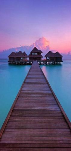 Maldives --Sunrise when the sky bursts into deep pinks and purples - looking out at the crystal clear waters surrounding Huvafen Fushi's overwater pier in the Maldives