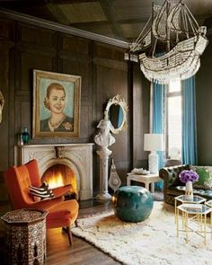 In the living room, a vintage Hans J. Wegner chair, a leather ottoman from Mecox Gardens, Ankasa pillows, and vintage cocktail tables from John Salibello; the chandelier is from Burden Antiques and Fine Works of Art, and the portrait of Eva Perón is a flea-market find.