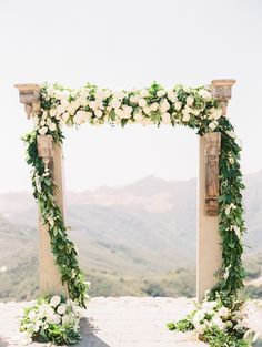 Stone arch covered in garland and flowers: http://www.stylemepretty.com/2016/09/06/neutrals-color-palette-malibu-wedding/ Photography: Sally Pinera - http://sallypinera.com/