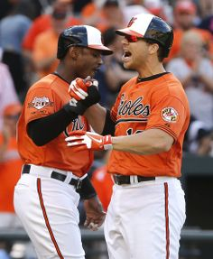 Adam Jones (L) #10 of the Baltimore Orioles celebrates with teammate Chris Davis (R) #19 as they score on Davis's 2-run home run in the fifth inning