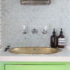 Gold bathroom sink with light blue patterned tiles