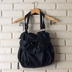 """Classic Black Elle Purse with Bow Everyone needs a black purse because it goes with everything! I have collected too many black purses which is why I am serving for a new home for this one. What I love most about this purse (aside from all of the secret compartments) is that it's photogenic! You heard me right, it looks soooo cute in pictures. The bow is a subtle feminine touch, it's just an effortless beauty- a great """"go to."""" Feel free to ask me any questions and let me know if you would…"""