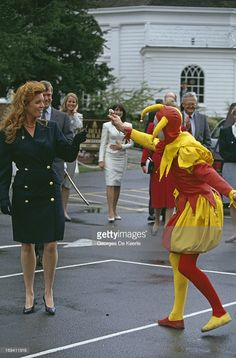 Sarah Ferguson, Duchess of York is handed a flower by a man dressed in a jester suit, circa 1991.
