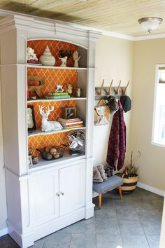 repurposed a hutch transformed into decorative shelves by painting it Martha Stewart's chinchilla grey and creating cardboard backing inserts with a pattern to mimic the look of wallpaper. It's a great piece to hold collections and also store practical everyday items in the cabinet below.