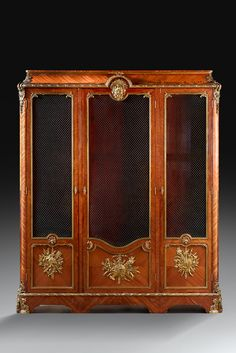 Large library veneer satin inlaid leaves in frames and violet wood. It opens with three partially screen doors. Rich and important bronze ornamentation finely carved and gilded, decorated depreciation, a mask of Bacchus radiant wearing a shell, in frames of sticks banded with clenched laurel leaves or water.