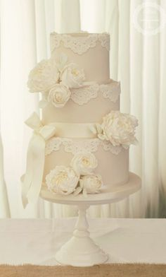 Classic three tier white lace detail wedding cake topped with white flowers; Featured Cake: Cotton and Crumbs