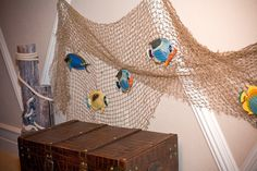 Tack a fish net to the wall and add a school of swimming fish, treasure chest, and pilings for a relaxing place for kids to play.