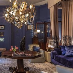 "A Warren Muller chandelier inspired by a ship wreck is the centerpiece of Louis Navarrete's Mischief Night room. Farrow and Ball's Drawing Room Blue sheathes the moody space. ""It's like Downton Abbey meets Comicon,"" says the designer of the bold but classic hue."