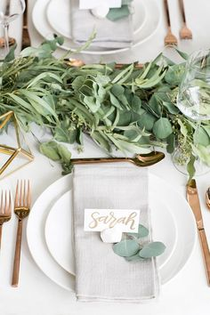 Beautiful table setting with eucalyptus for greenery, whtite dishes, gold utensils, and light gray cloth napkins.