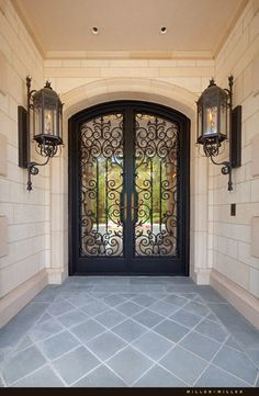 Custom ornate handmade wrought iron and glass front entry double door with custom gas lanterns. Ryan and Sarah Miller Realtors Photography by Miller + Miller Architectural Photography