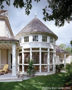 A rounded porch with conical roof and clerestory windows is reminiscent of the turrets of vintage shingle-style houses.