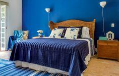 Quarto do casal   Azul domina a parede com arandelas da Reka e complementos. A cama tem cabeceira de fibra de málaca da Artefacto Beach & Country, mesma loja dos baús. Roupa de cama e manta da Blue Gardenia e almofadas do Studio Bergamin. (Foto: Edu Castello/Editora Globo)