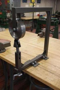 Homemade English wheel fabricated from steel plate, rod, and square tubing. Equipped with a commercial upper anvil and a pillow block bottom anvil.