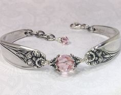 This delicate spoon bracelet was created from two vintage teaspoons. The pattern is the ever popular Daffodil from 1950. The spoon bracelet is adorned with a sparkling 10mm light pink swarovski crystal which is attached with twists of sterling silver wire with two sterling silver flower bead caps for detail. The crystal creates a soft yet striking effect against the silver. The spoon bracelet is finished with an Italian sterling silver lobster clasp. There are also extra rings for an…