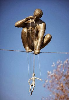 Jerzy Kedziora amazing whimsical contemporary street art installation conceptual performance sculpture in bronze of the puppet master up on a wire how it is done I know not but its blooming brilliant