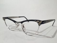 Incredibly well-preserved and stellar, classic aluminum cateye frames. Made by Artcraft, these are stunning Eyeglass or Sunglass Frames! Black aluminum frames that feature beautiful silver and gold etched design. They are New Old Stock Frames. Never used & ready for your prescription. Dont forget these would also make a fabulous pair of sunglasses, too. No need to pay $150 or $175!! Here they are NOS, at a very reasonable price. If you bought eyeglass frames anywhere else then you paid to...