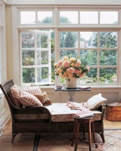 Gorgeous reading spot by window with a large vase of flowers on a small occasional table, with an antique rattan chaise