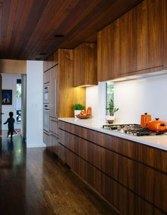 A midcentury home features a kitchen with a polished quartz countertop and walnut cabinets.