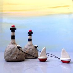 Miniature ceramic lighthouse with a little ceramic boat , miniature ceramic sculpture by Edna Piorko.