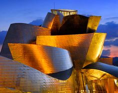Guggenheim, Bilbao.  FRANK GEHRY.  The Guggenheim Museum Bilbao is the benchmark of Canada-born Frank Gehry's career. In 1997, this jaw-dropping structure transformed an unknown industrial Spanish town that had fallen on hard times into an internationally recognizable destination. The Guggenheim Bilbao's colossal, titanium-clad dimensions grace the Nervión's riverbank like an ocean liner from a futurist's sketchbook, reflecting the building's graceful contours in the muddy water below.