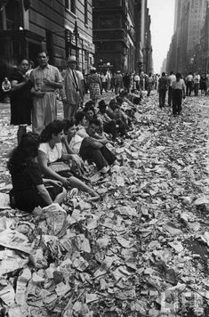 People sitting on curb among confetti and paper after celebrating the end of WWII in NYC on August 14, 1945.